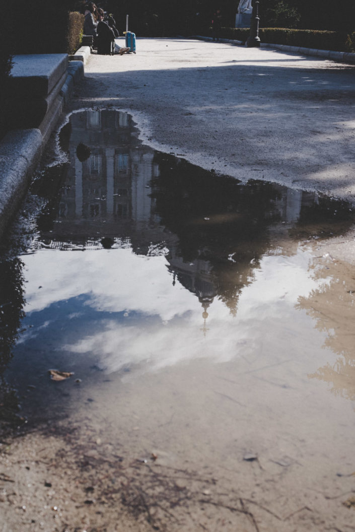 Street photography of the Royal Palace of Madrid as seen upside down from a puddle, street photography del Palazzo Reale di Madrid visto capovolto da una pozzanghera