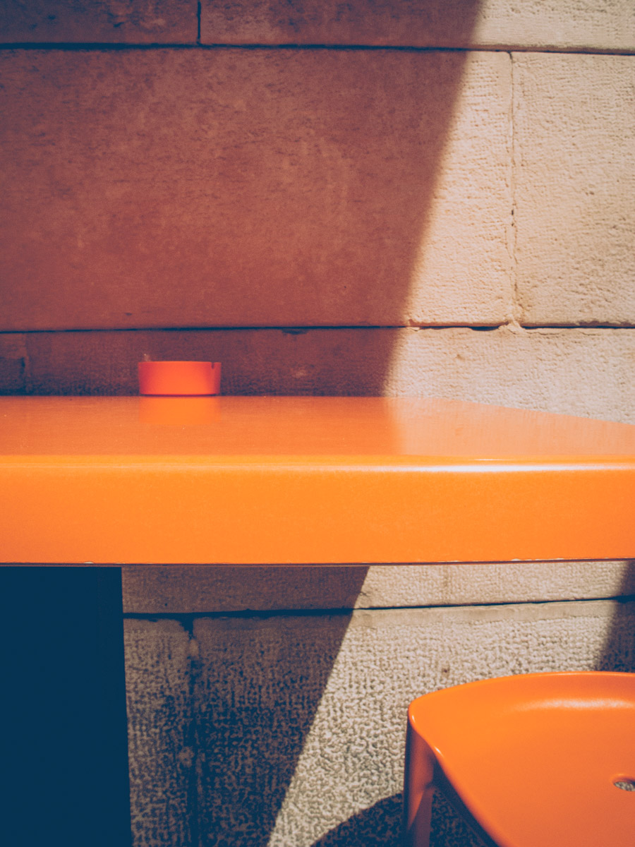 a detail of an orange bar table and chair with a black shadow in barletta