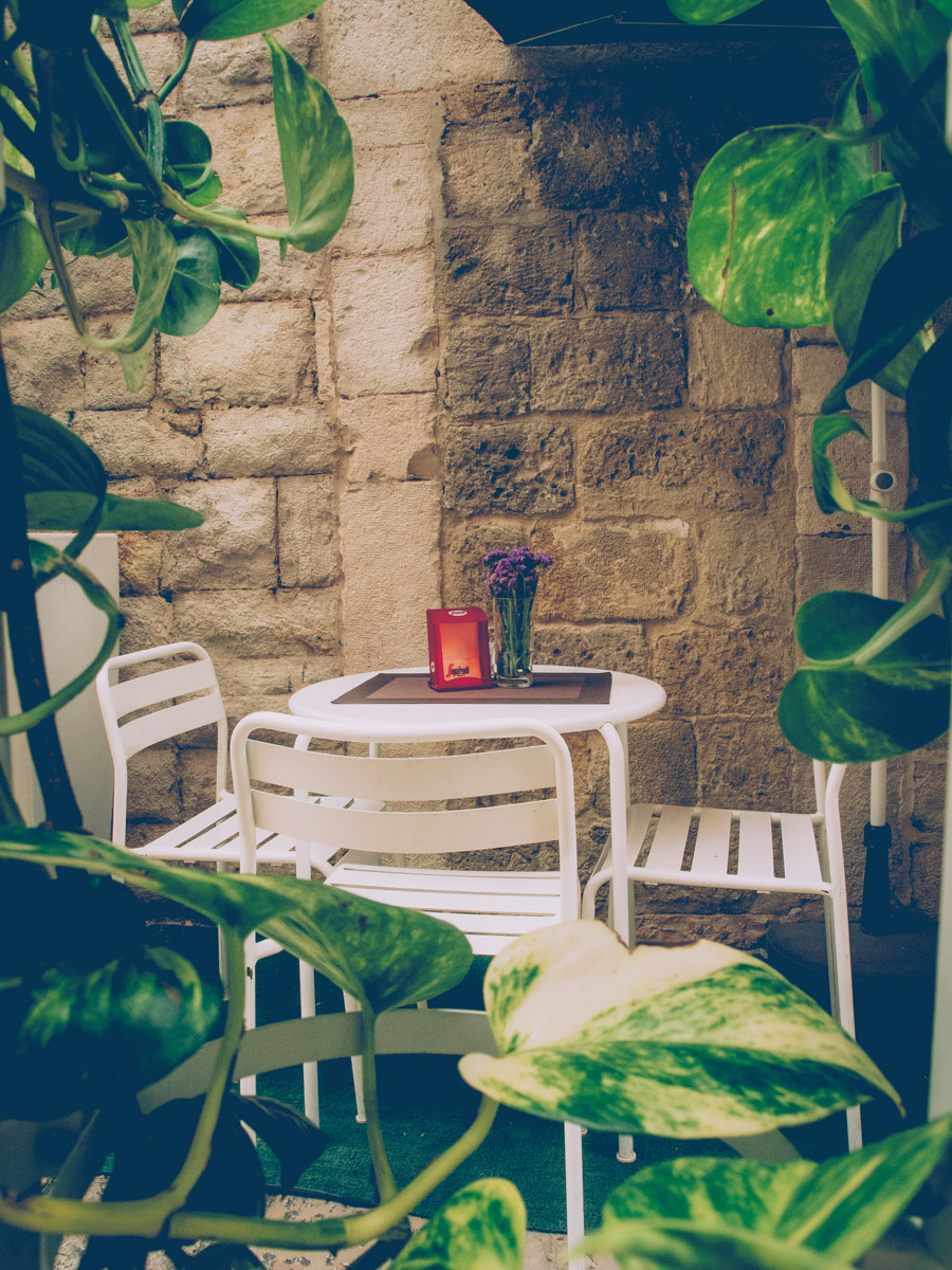 an ampty white bar table and chairs in Barletta surrounded by green leaves