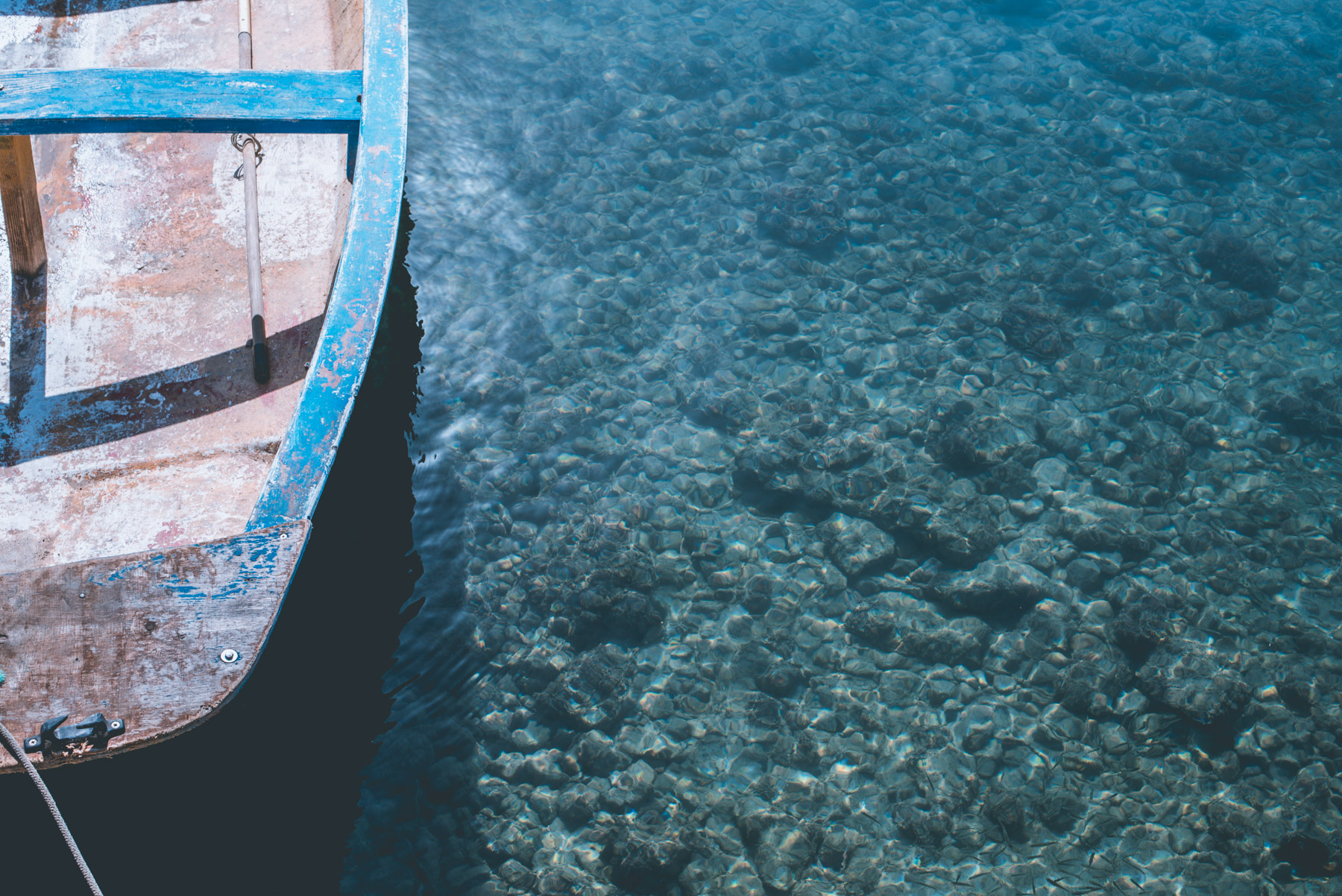 Detail of the blue sea of the island of lampedusa and a small section of a wooden boat