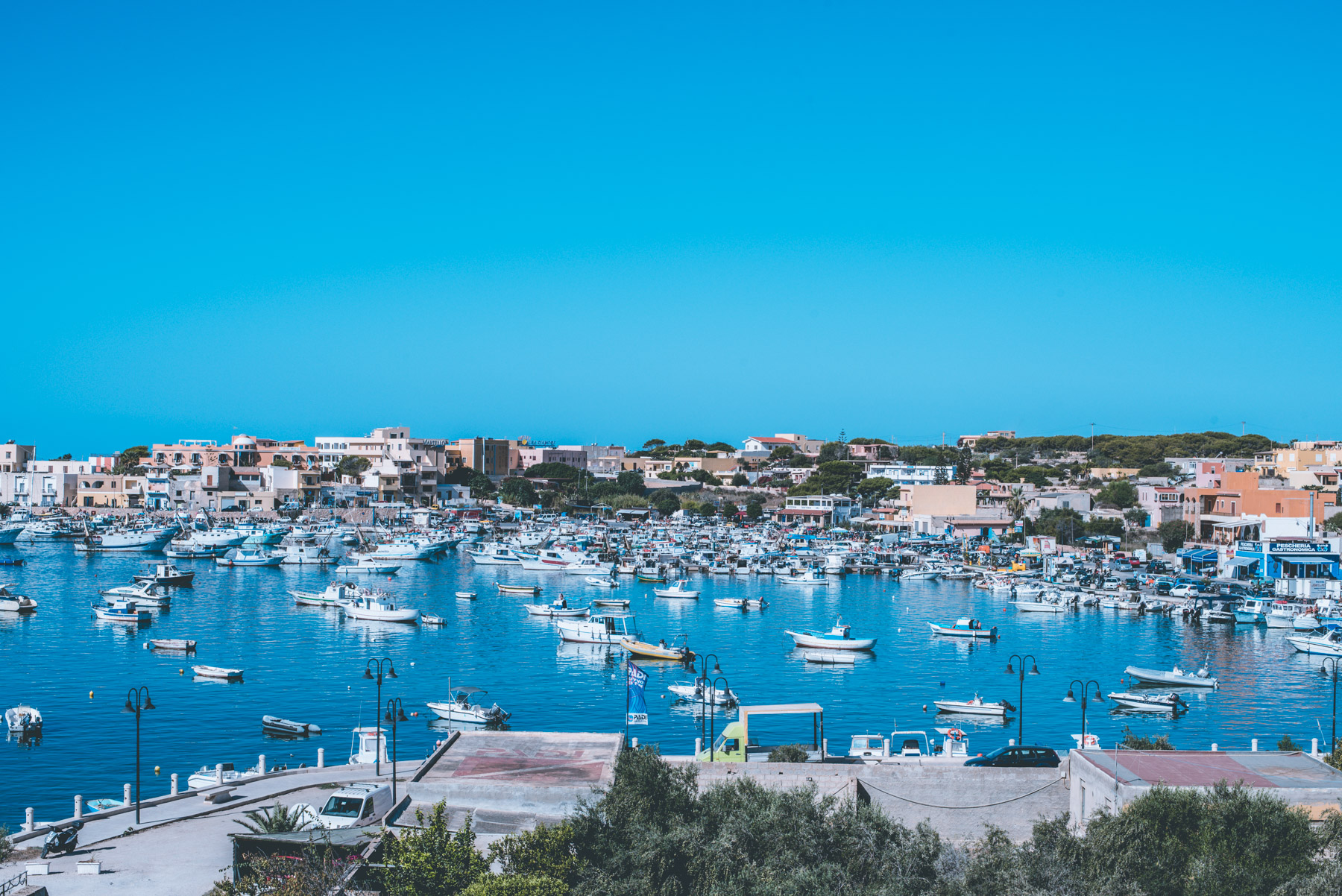 a panoramic view of the harbour of lampedusa with houses blue sea and white boats