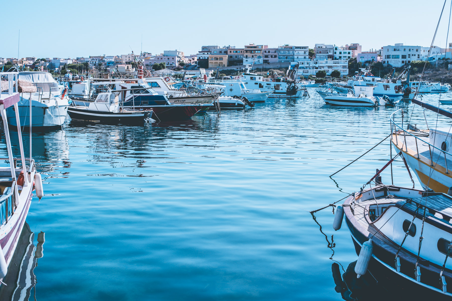 the harbour of Lampedusa with the blue sea and many boats