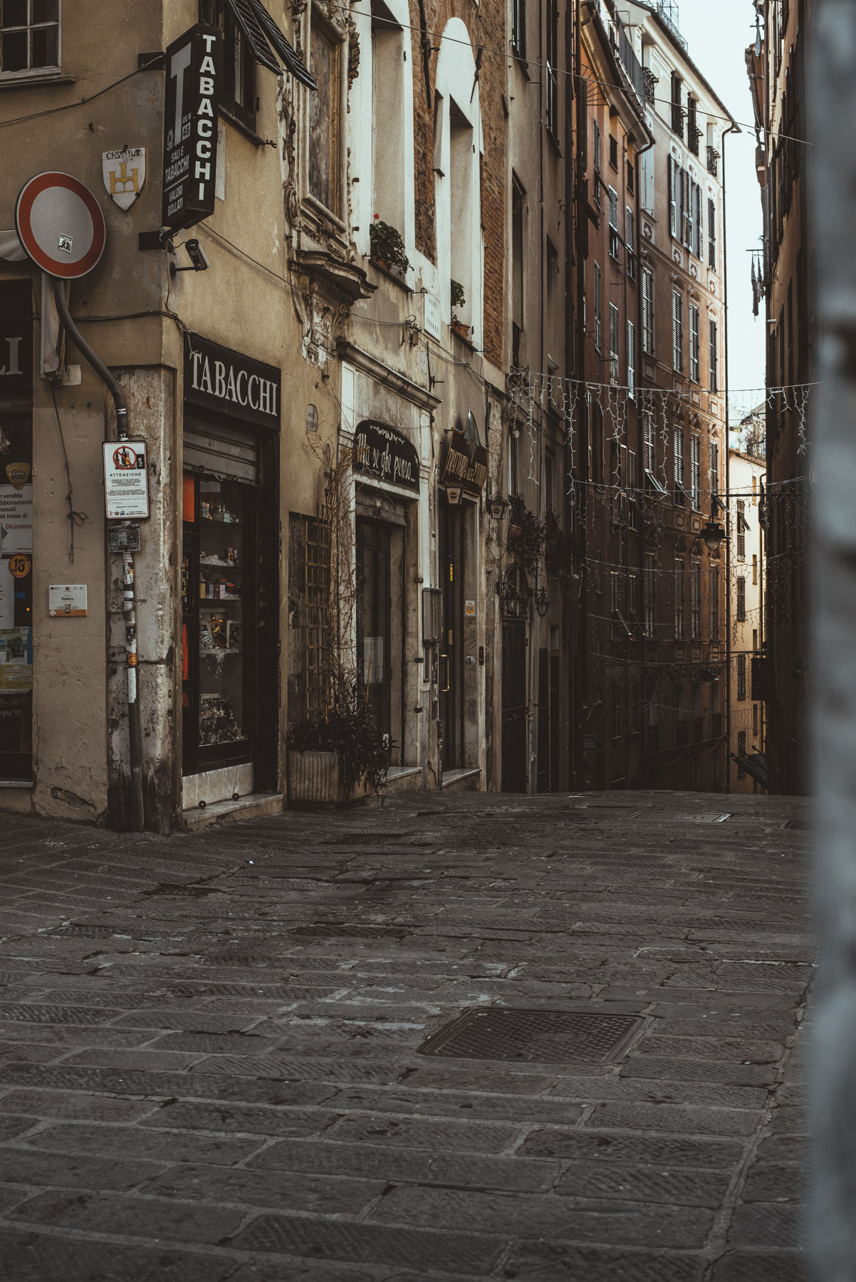A street photograph that shows caruggi streets in the old town of Genoa