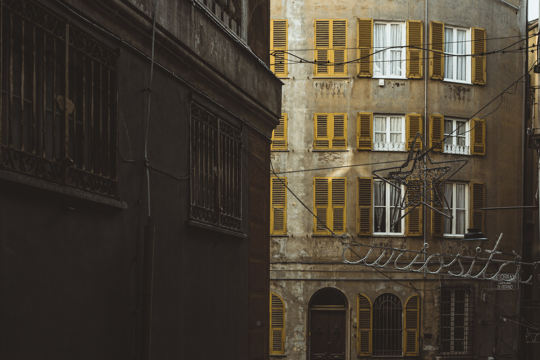 A detail of one building with yellow windows in the old town of Genoa