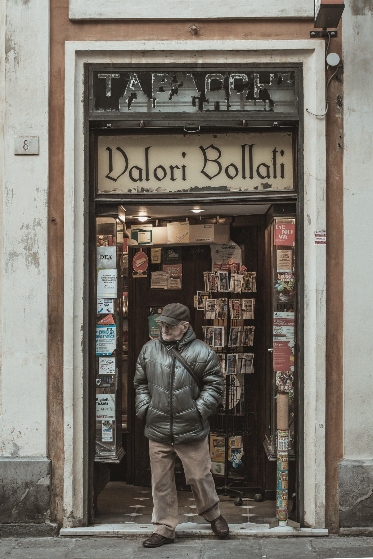 a man exiting an old shop in the old town of Genoa