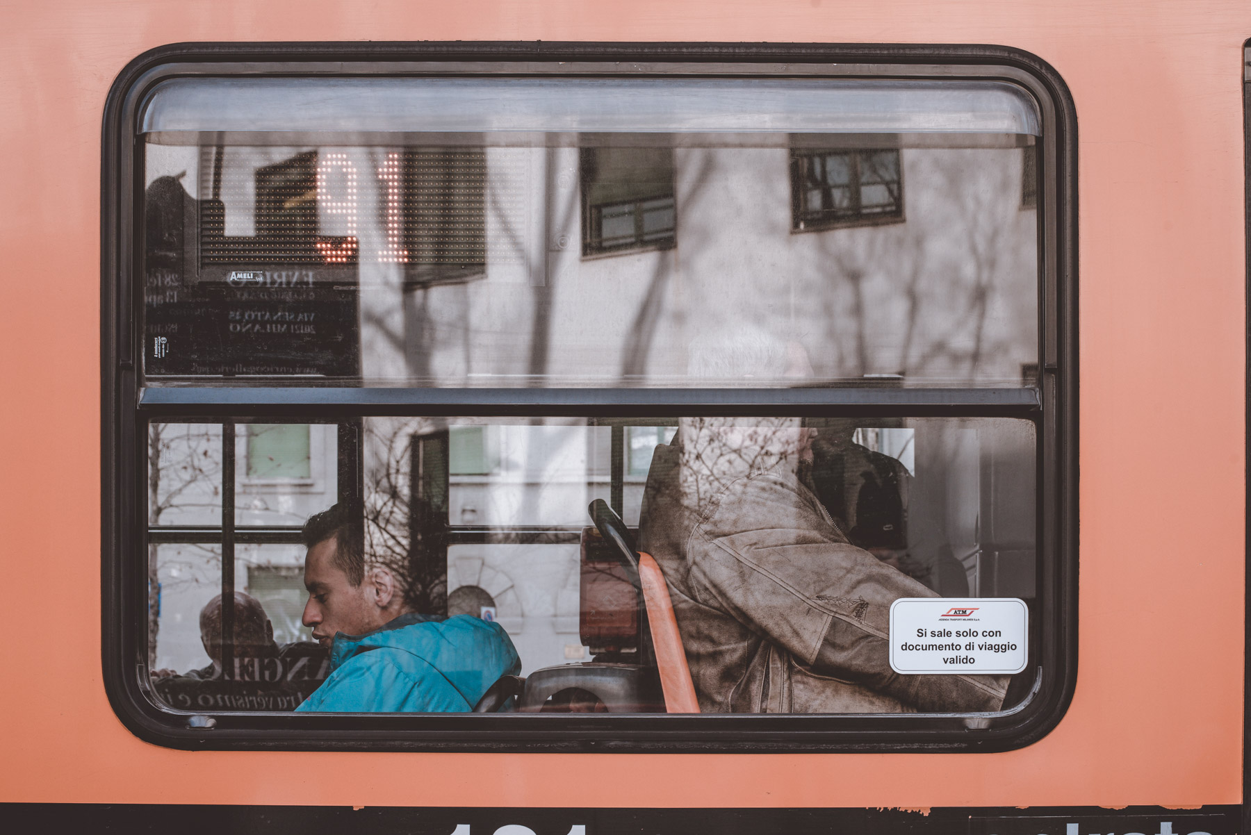 a street photograph showing some reflections and some people on the bus in the city of Milan