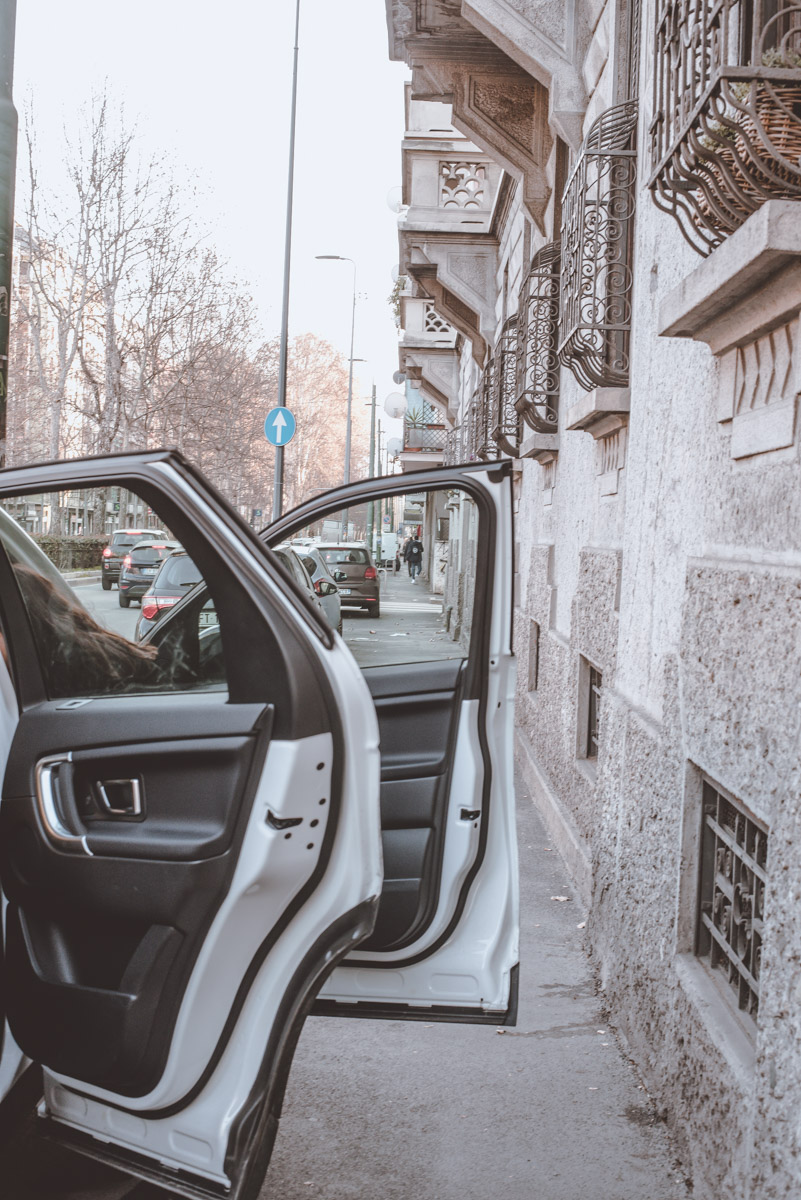 A street photograph showing some car doors open in the city of Milan