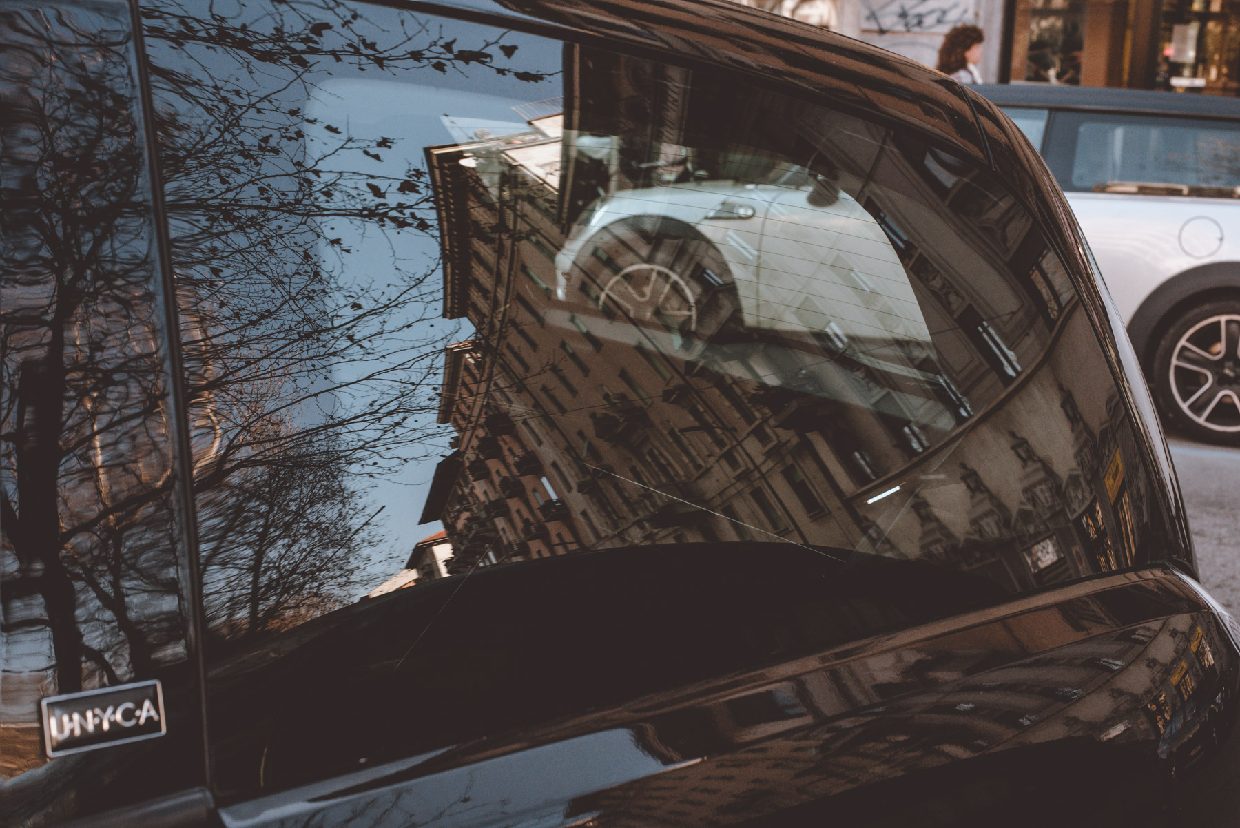 A street photograph showing reflections of a car some buildings and trees on the streets of Milano