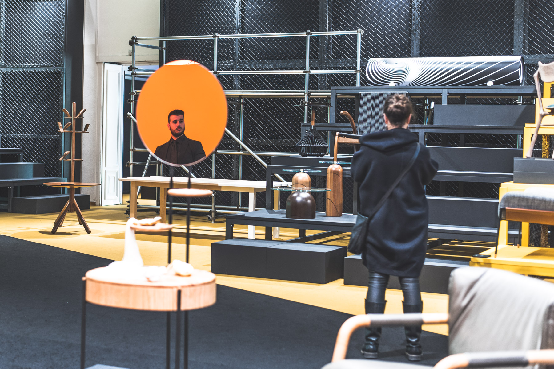 A photograph showing the reflection of a man in a mirror and somebody watching furniture during Fuorisalone Milan Design Week 2019