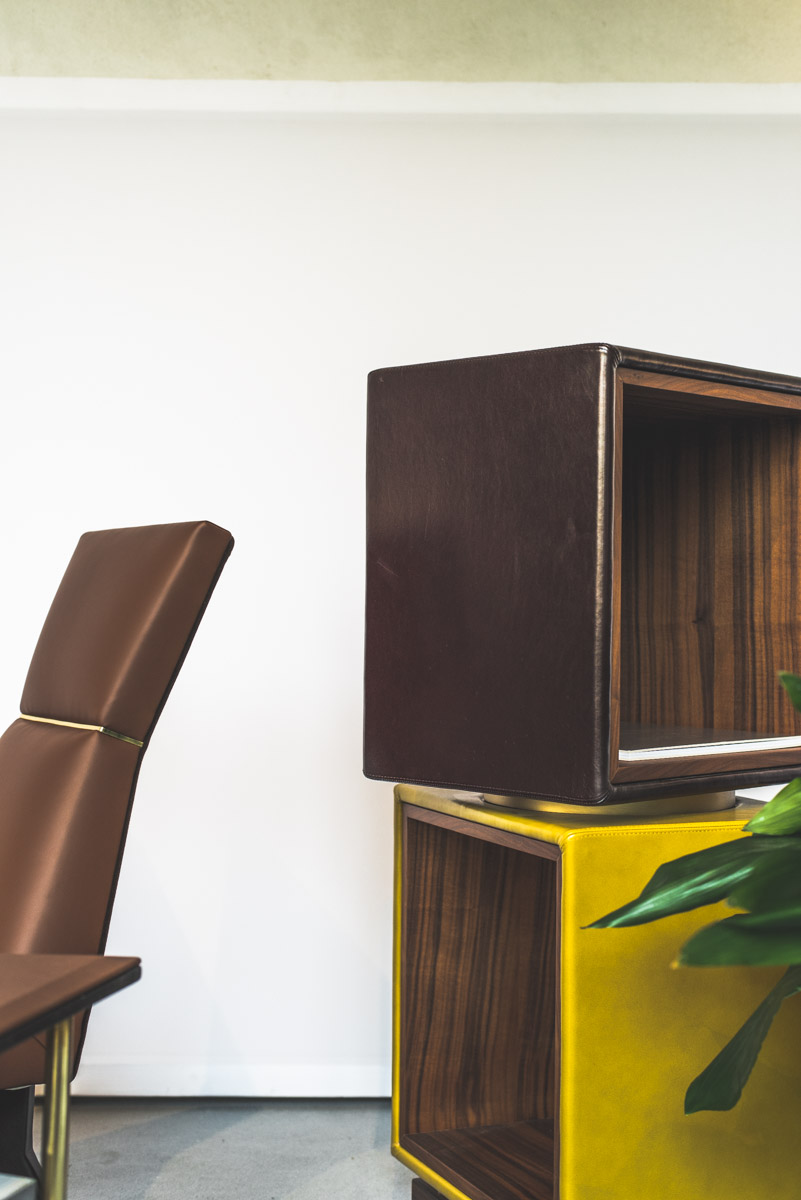 Brown leather chair and a library made of brown and yellow cubes during Fuorisalone Milan Design Week 2019