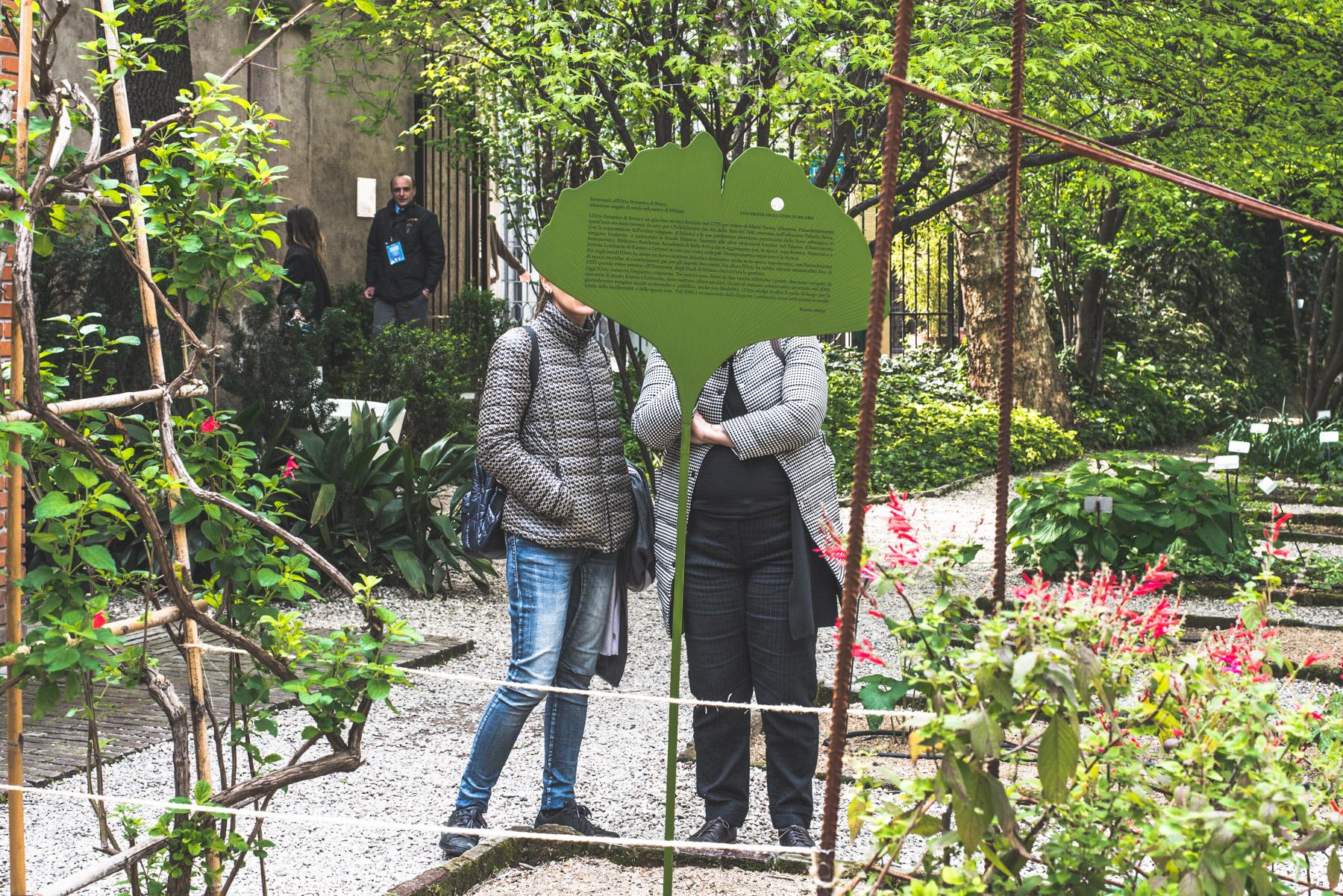 Two women watching a poster in the Brera Botanical Gardens during Fuorisalone Milan Design Week 2019