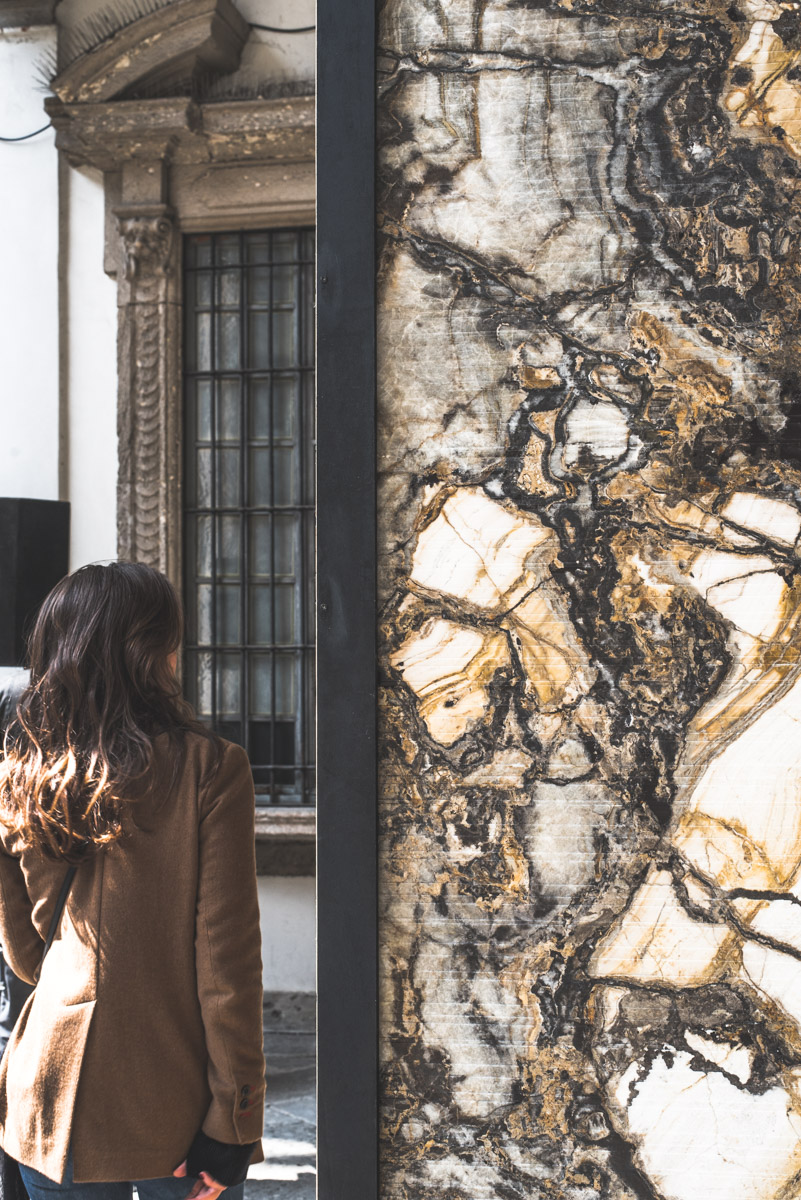 A girl walking near a brown patterned marble during Fuorisalone Milan Fashion Week 2019