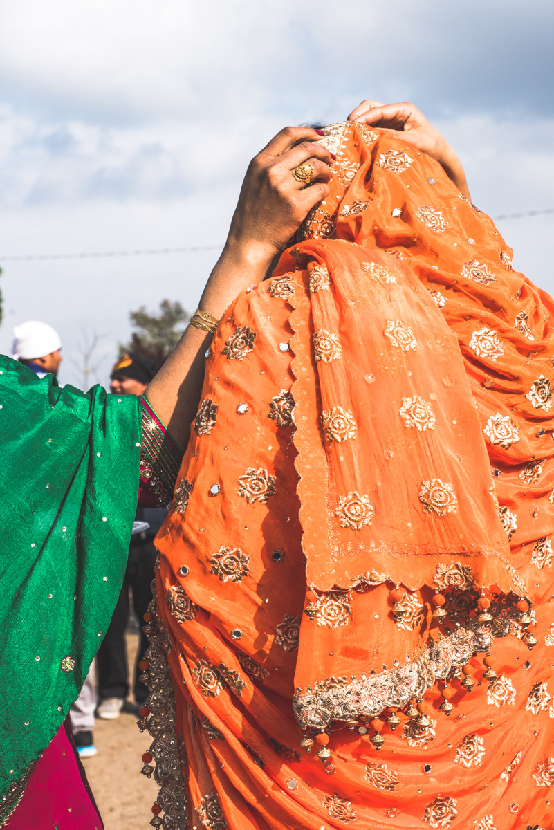 Detail of a bright orange and golden veil worn by a Sikh woman attending Vaisakhi in Novellara