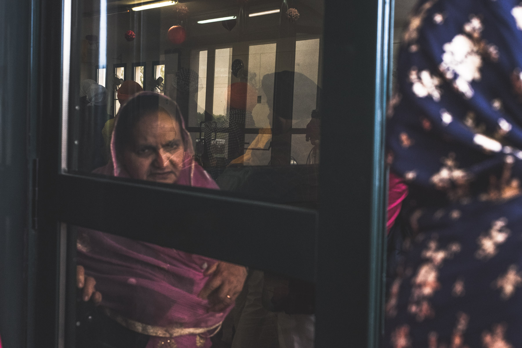 Al old Sikh lady solemny looking ahead of her through a window while attending Vaisakhi in Novellara