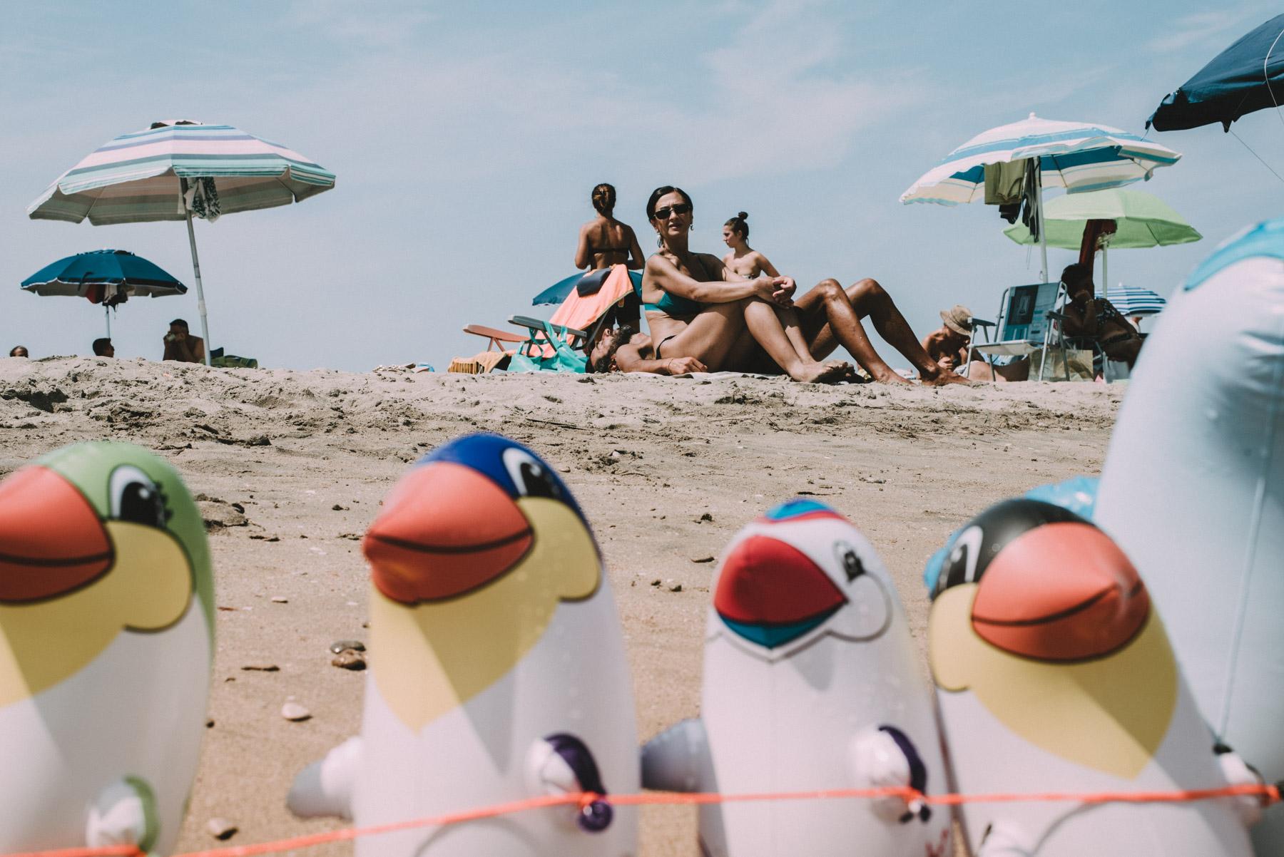 a lady on the beach by the sea framed by rubber beach toys in the city of Barletta in Apulia, una signora in spiaggia al mare con in primo piano dei giocattoli da spiaggia di gomma nella città di Barletta in Puglia
