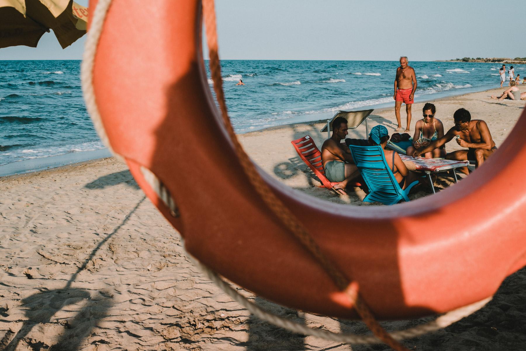 Some friends having fun and playing cards on the beach by the sea in the city of Barletta in Apulia, alcuni amici si divertono in spiaggia giocando a carte vicino al mare nella città di barletta in Puglia