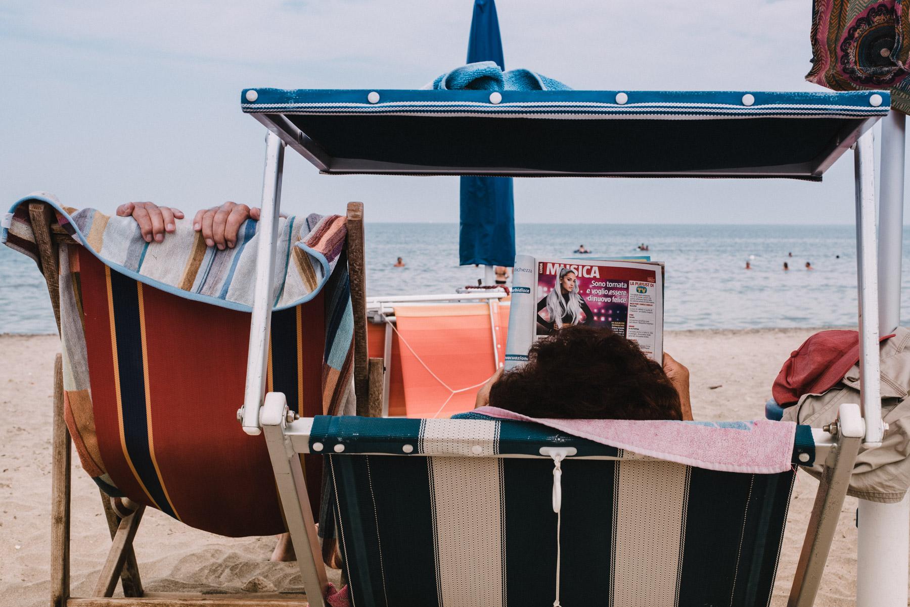 Two people having relaxing time sitting on the beach by the sea whatching the sea and reading a magazine in Barletta Apulia, due persone si rilassano in spiaggia davanti al mare e una legge una rivista a Barletta in Puglia