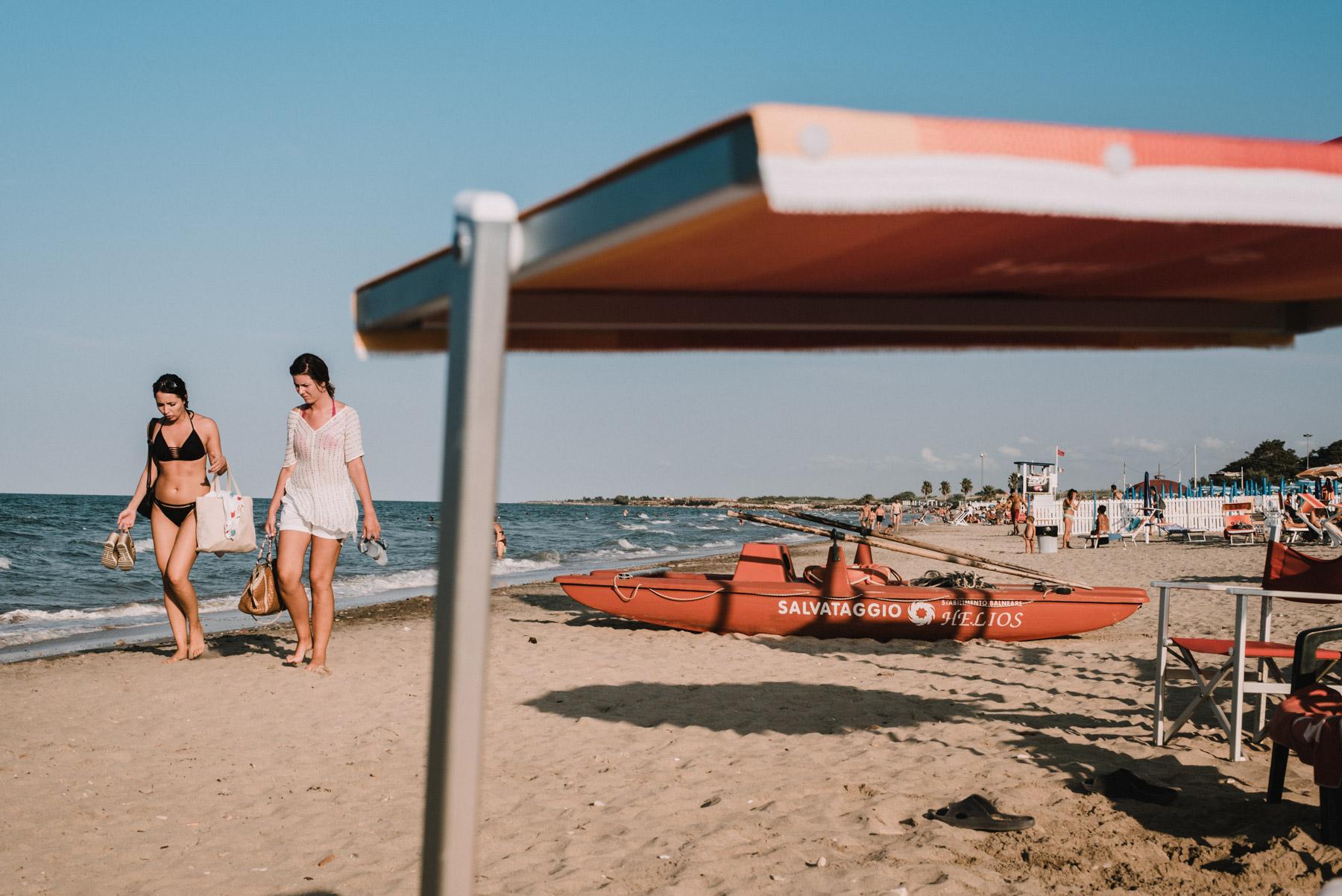 two girls having a stroll on the beach by the sea in the city of Barletta in Apulia, due ragazze fanno una passeggiata in spiaggia al mare a Barletta in Puglia