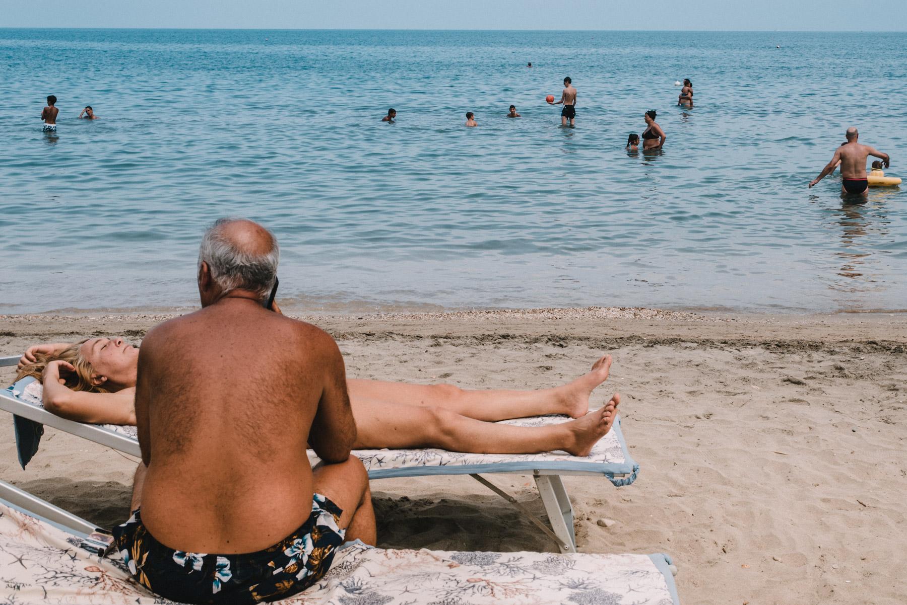 a couple having some relaxing time at the beach by the sea in the city of Barletta in Apulia, una coppia si rilassa in spiaggia durante una giornata al mare a Barletta in Puglia