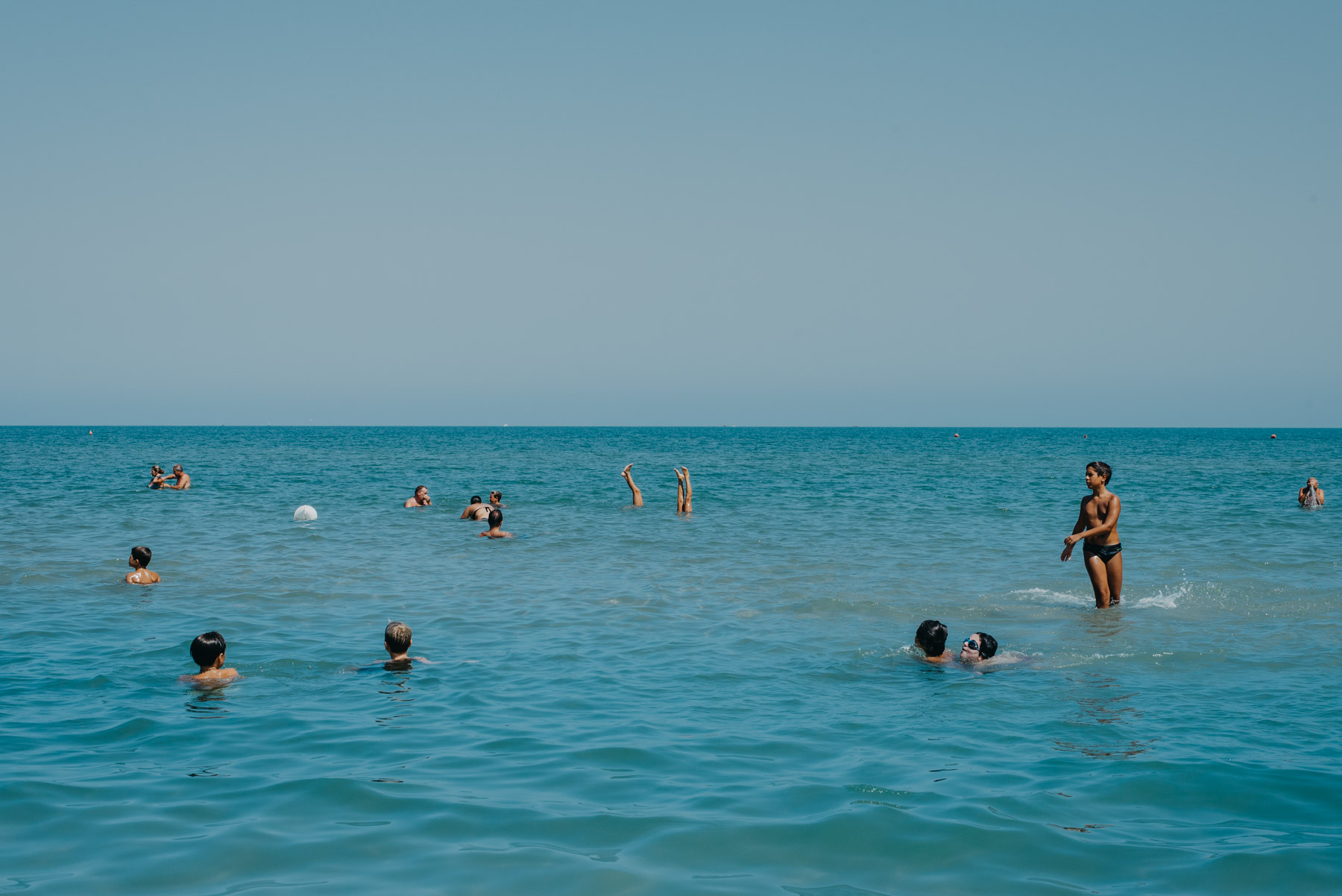 People anche children playing at the beach in the blue sea in the mediterranean sea in the city of Barletta, Apulia