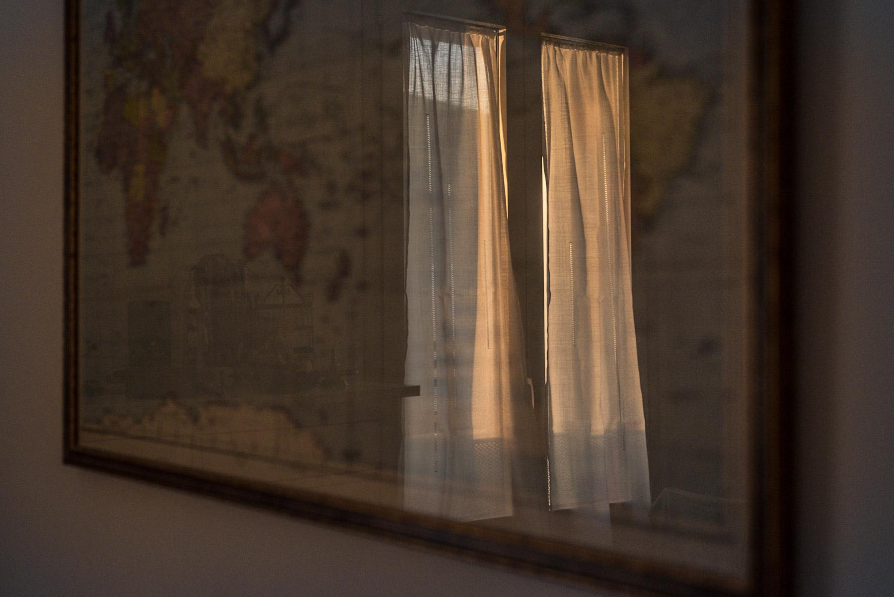 The shadow of a window over a framed map of the world / il riflesso di una finestra si vede da l vetro della mappa del mondo in cornice.