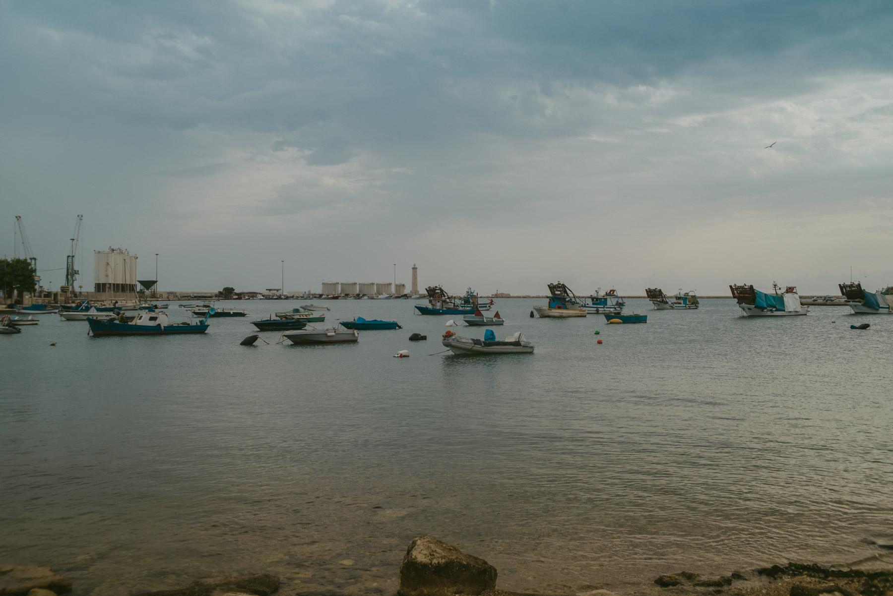 Il porto a barletta con barche piccole in una giornata calma e grigia e nuvolosa - The harbour of Barletta with small ships during a grey moody and cloudy day