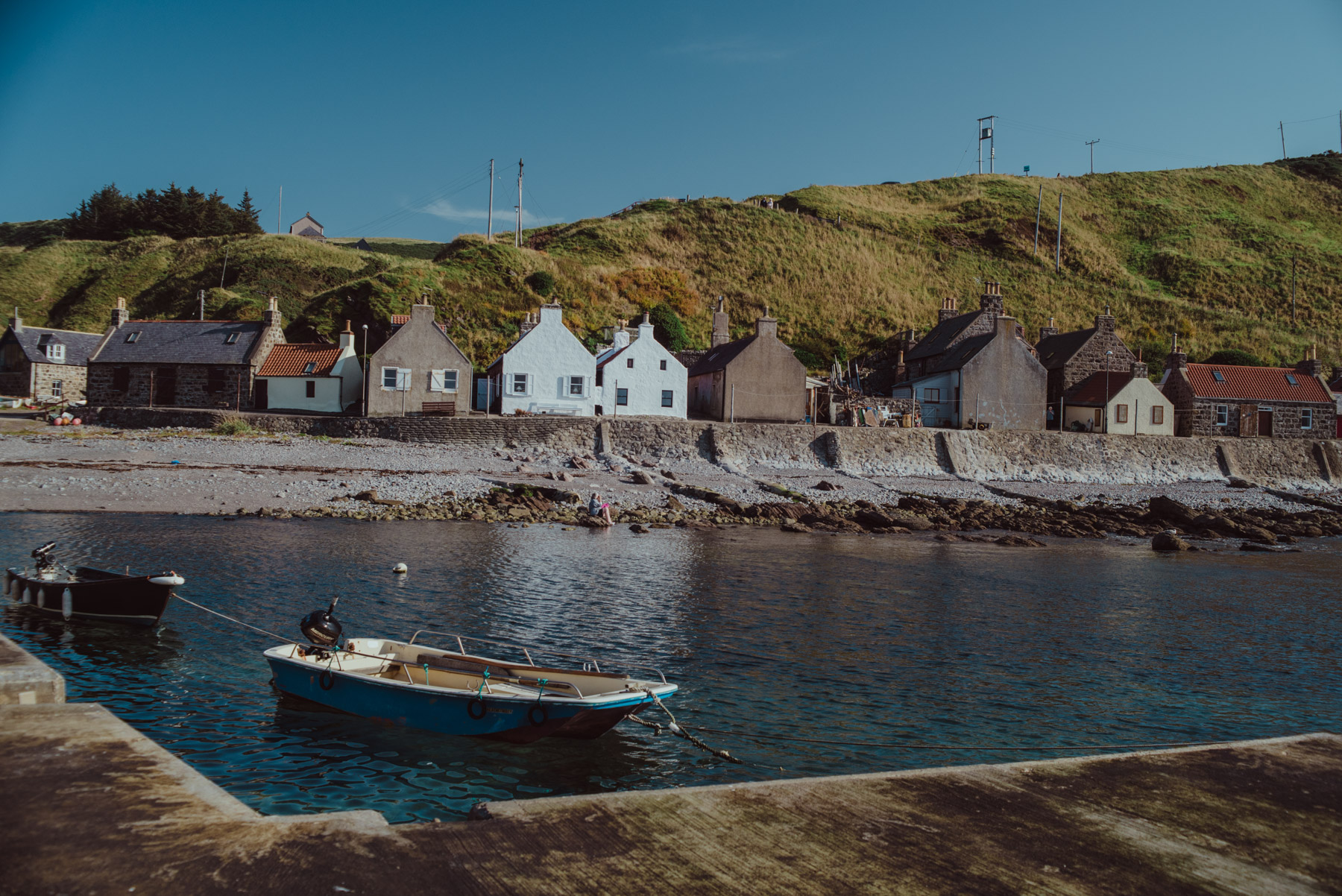 A small boat hangs in the water in the little harbour of Crovia, a small village in Scotland, una piccola barca si trova nel porticciolo del villaggio di Crovie in Scozia