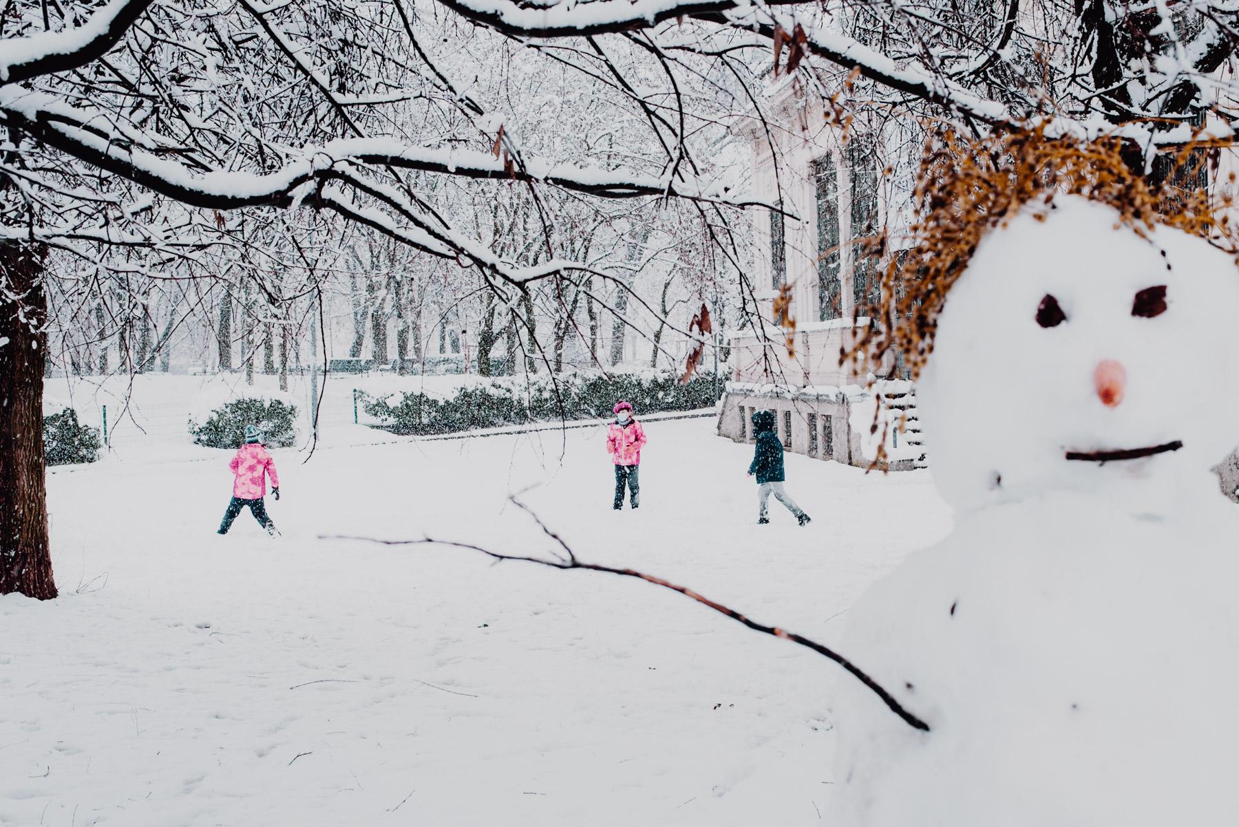 Snow in Milan on December 2020, in Formentano Park there's s snowman and two children playing snowball fights in the background, neve a milano a dicembre 2020 nel parco Formentano al Largo Marinai d'Italia un pupazzo di neve in primo piano svela due bambini che giocano lanciandosi palle di neve sullo sfondo