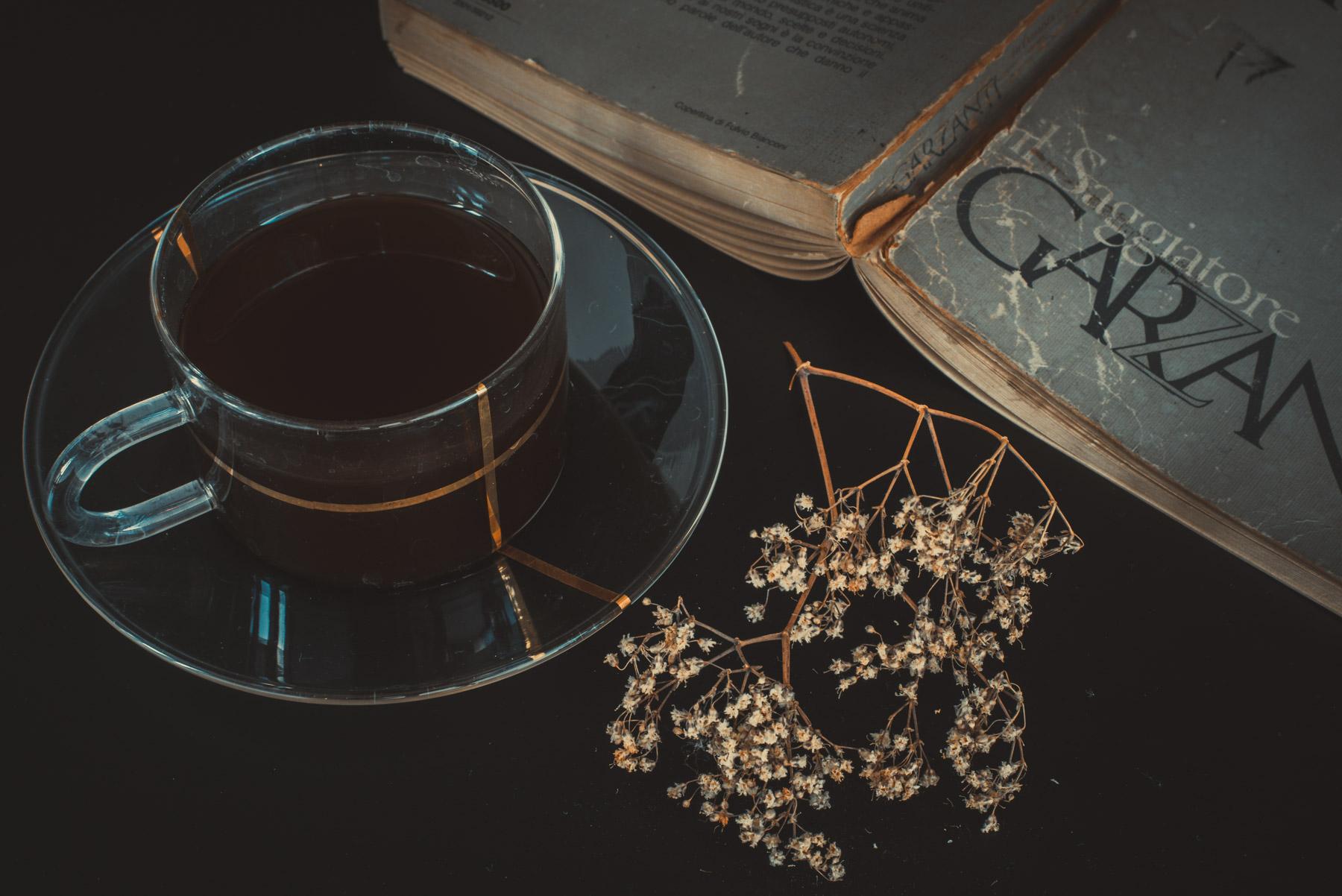 A coffee cup on a dark table with an old open book and white dried flowers; una tazza di caffè su un tavolo scuro con dei fiori secchi chiari e un vecchio libro aperto