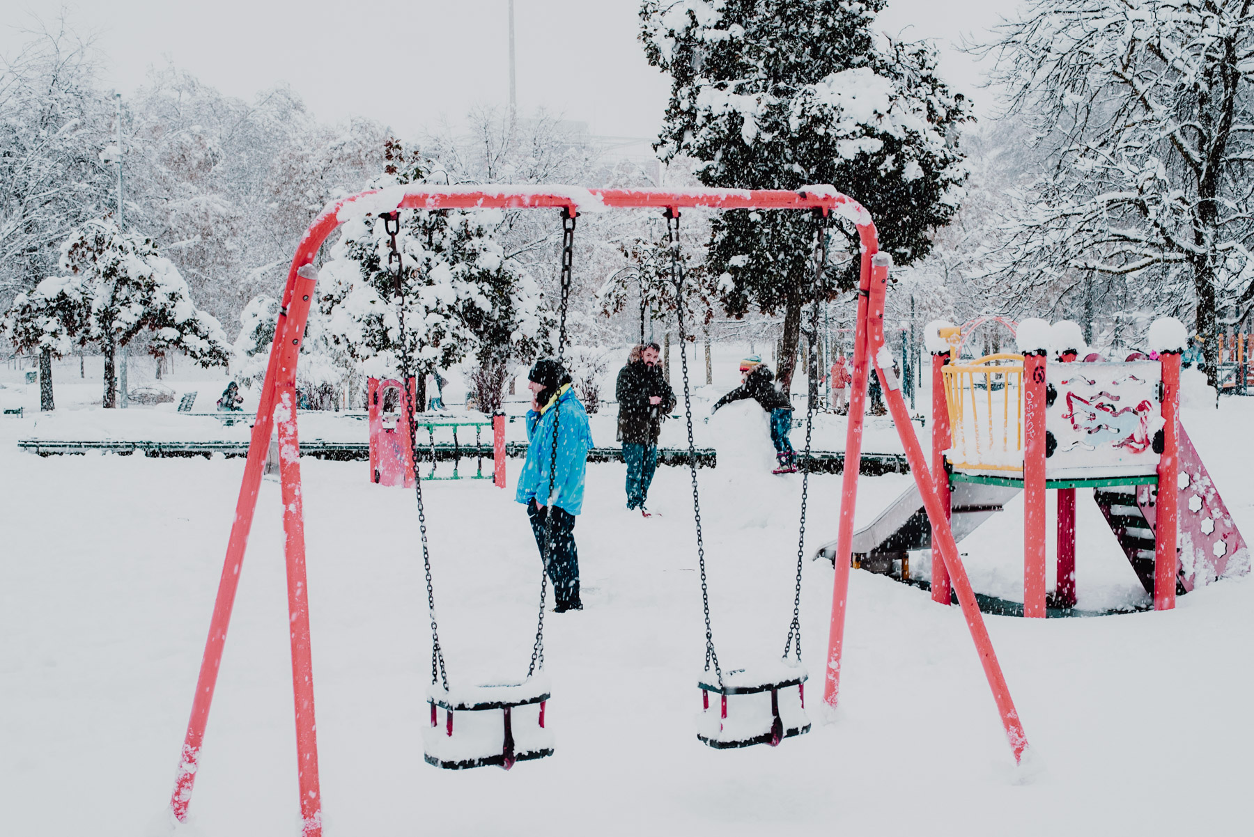 Snow in Milan on December 2020, people standing and talking in the middle of a playground, neve a Milano a dicembre 2020, persone si trovano per giocare e parlare nell'area giochi per bambini