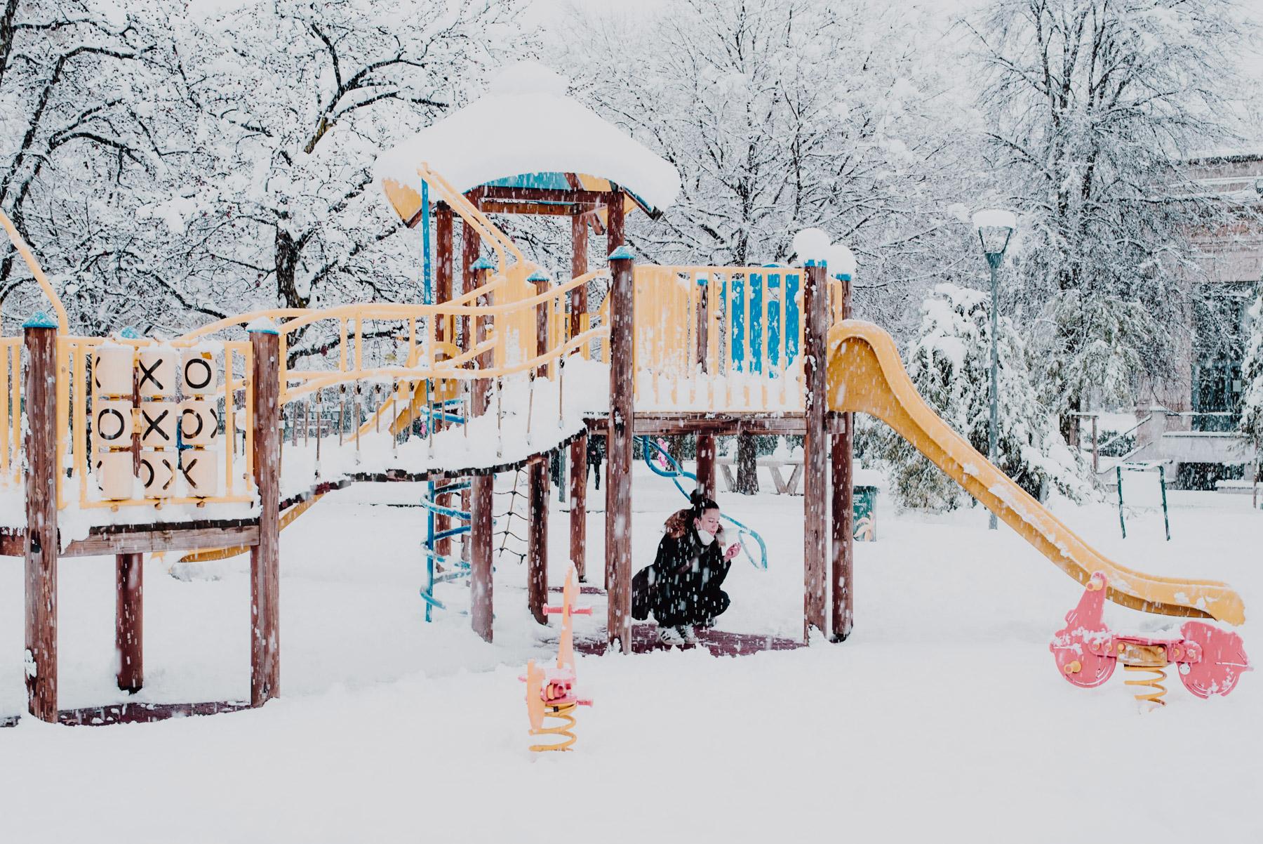 Snow in Milan on December 2020, a girl shields from the snow below the play area in a park, nevicata a Milano il 28 dicembre 2020, una ragazza cerca riparo dalla neve sotto lo scivolo dell'area giochi per bambini al parco Formentano presso Largo Marinai d'Italia