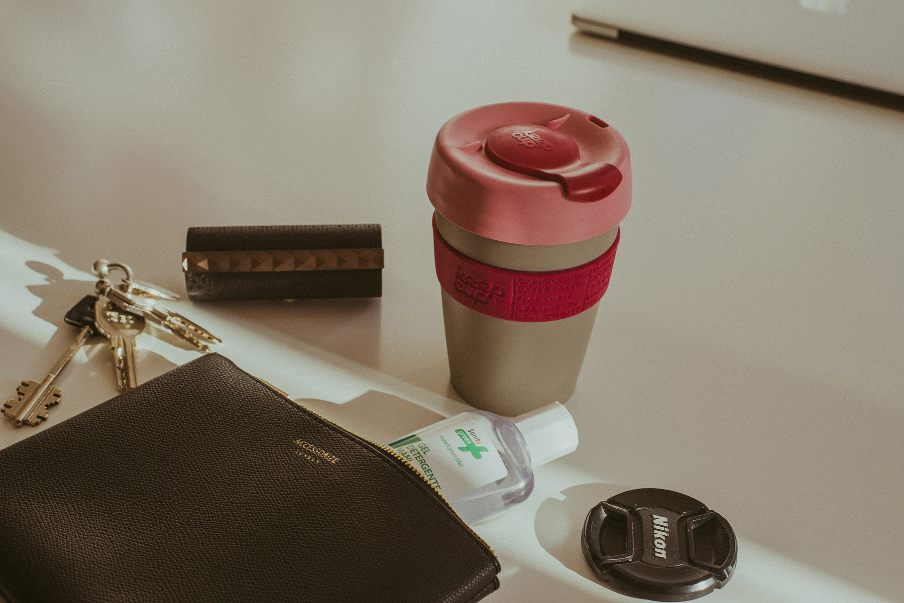 Keep Cup mug in pink and grey an a table with an Accessorize pouch, keys, hand sanitizer