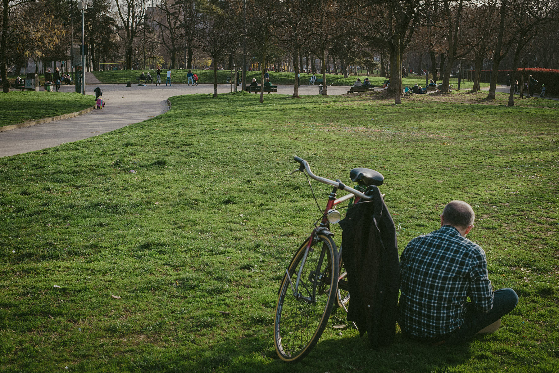 A man sat on the grass alongside his bicycle in the Vittorio Formentano Park in Milan