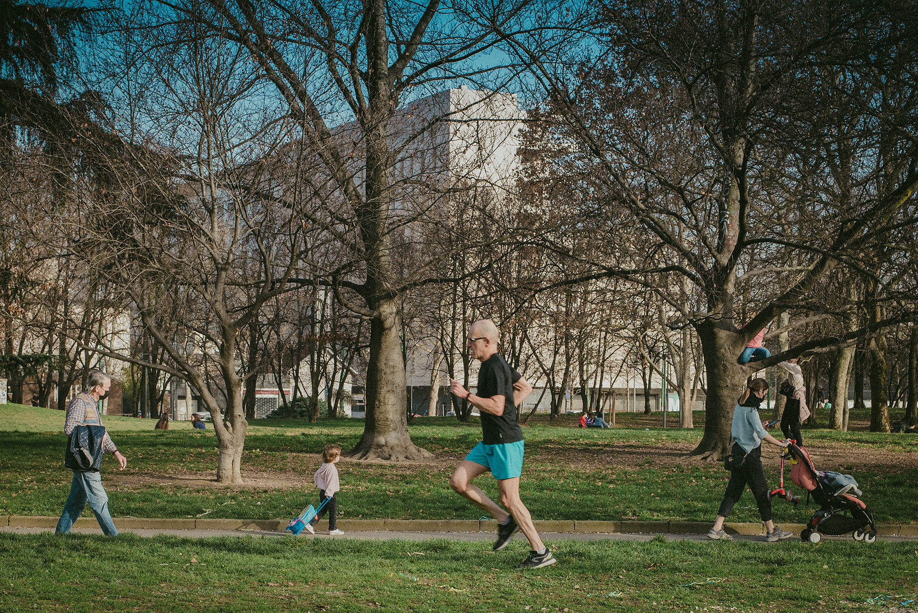 A man running in Vittorio Formentano park in Milan, while some persons walk by