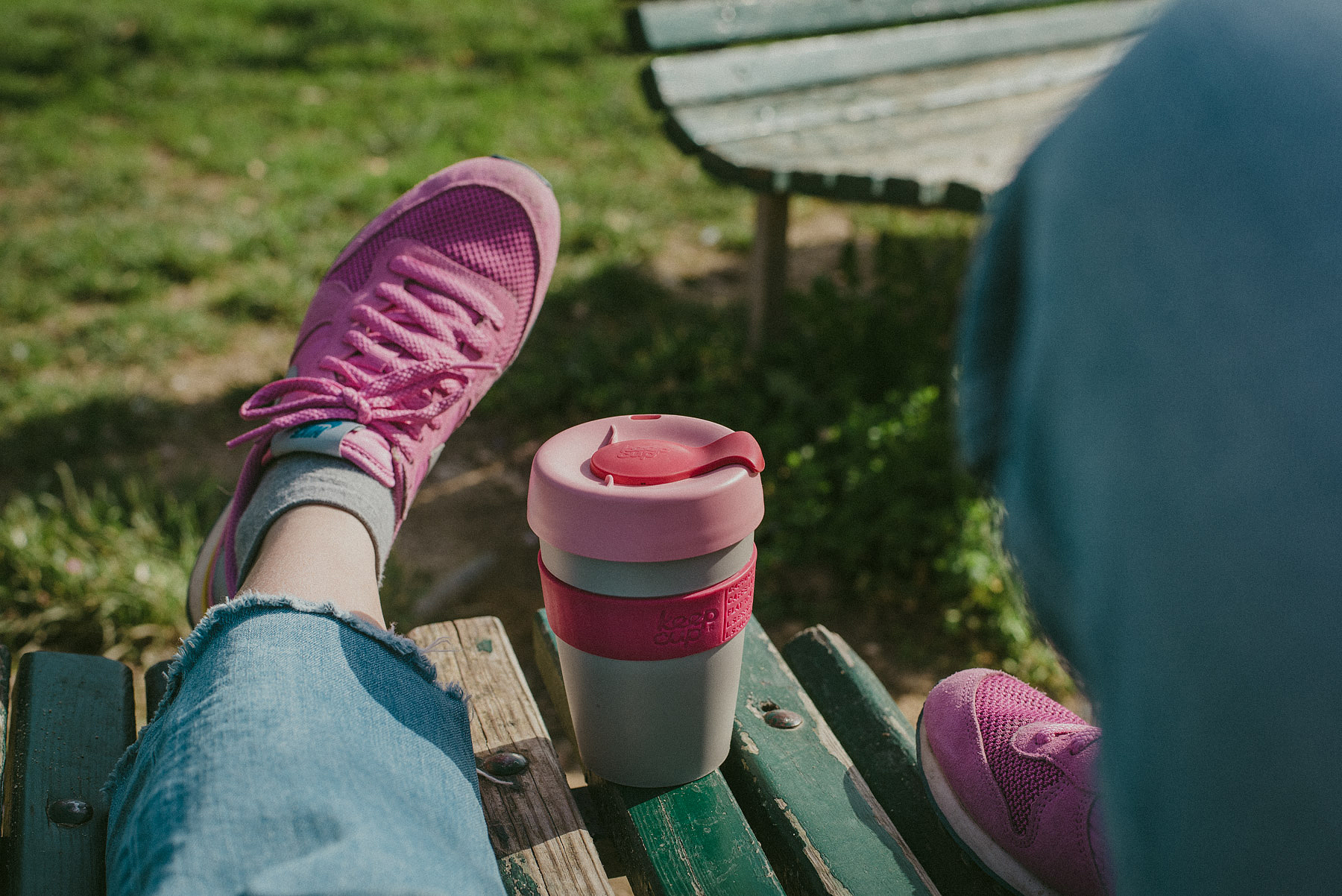 A Keep Cup mug on a park bench while relaxing with some NIke shoes on